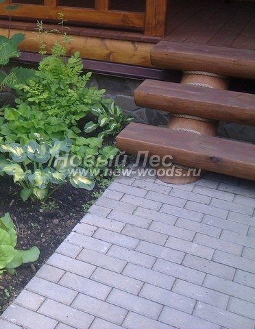 Брусчатка возле входа в дом уложена на клеевой раствор на бетонную подушку рядами со сдвигом на половину плитки (в данном случае бордюр не требуется)