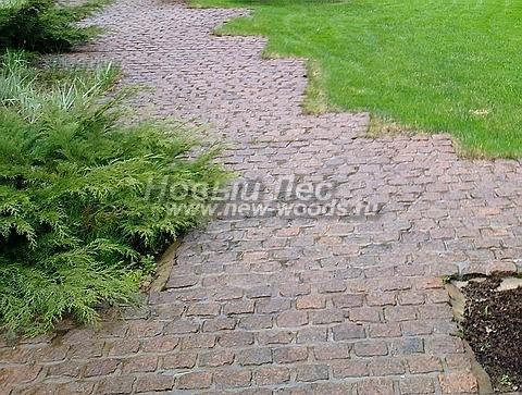 Колотая гранитная брусчатка красновато-коричневого цвета, уложенная на бетонную подушку и цементный раствор