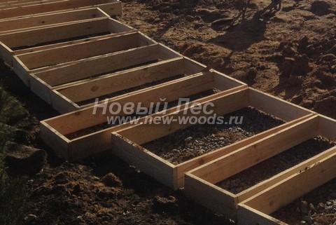 Один из этапов строительства садовой дорожки из гранита: на песочно-щебёночную подложку установлены опалубки для заливки бетонных подушек индивидуально для каждой гранитной плиты (слэба)