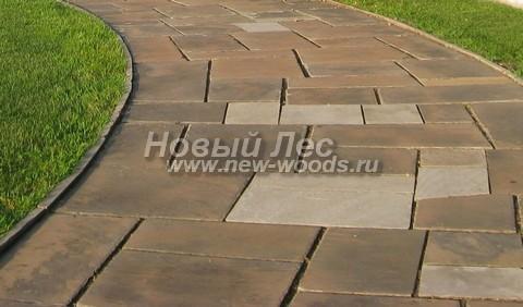 Парковая дорожка большой ширины, в которой конструкция из каменных плит удерживается каменными бордюрами