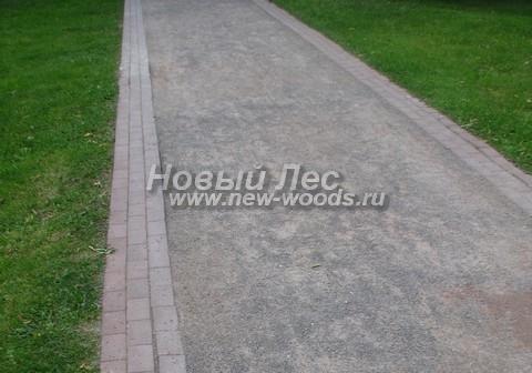 Дорожка из гранитного отсева с тротуарной плиткой по краю, которая исполняет роль бордюра