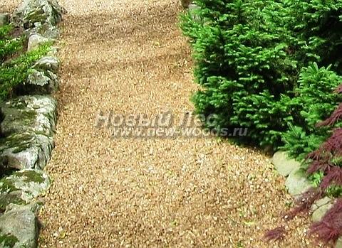 Садовая дорожка из гравия со светло-коричневым оттенком, ограниченная бордюрами из натуральных камней-валунов