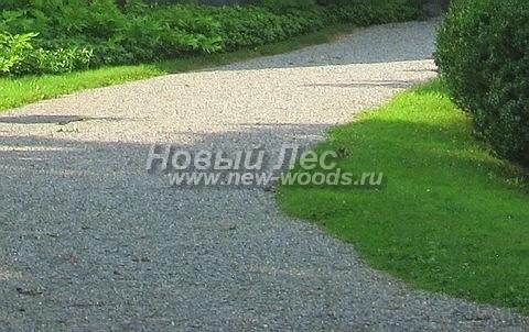 Дорожка на участке возле загородного дома с отсыпкой из гравийного отсева светло-серого цвета, рассчитанная и на проезд автомобилей