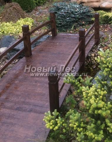 Мостик с перилами из дерева, перекинутый через ручей