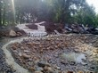 Строительство искусственного водоема и альпийской горки под ключ: создание русел ручьев, впадающих в водоем, и начало декорирования склонов горки большими камнями